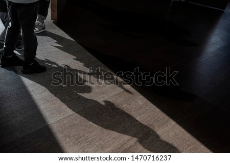 Opened Door and Shadows of Children talking about something in a small Room - picture about mystery play secret
