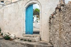 Opened door in old abandoned wall, Crete island, Greece