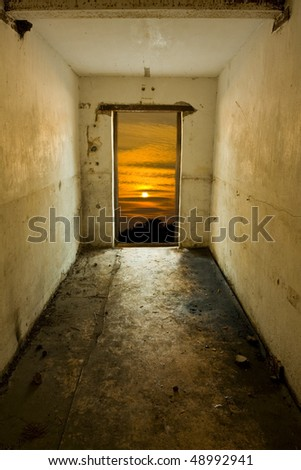 Opened door of abandoned house to sunset