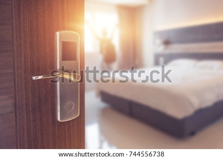 Opened door of hotel room in morning with background blurred happy backpacker traveller stay in hotel, sunlight effect. #744556738