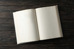 Opened empty book on wooden background, space for text