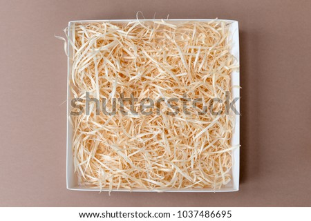 Opened gift box with decorative straw, filler, shavings. #1037486695