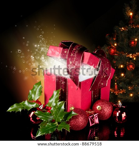Opened gift with shiny bubbles inside and christmas tree on background