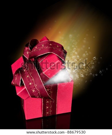 Opened gift with shiny bubbles inside, isolated on black background