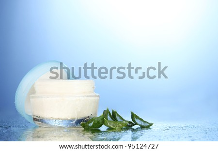 Opened glass jar of cream and aloe on blue background with water droplets