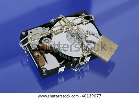 Opened hard disk secured with an iron chain and padlock on blue background
