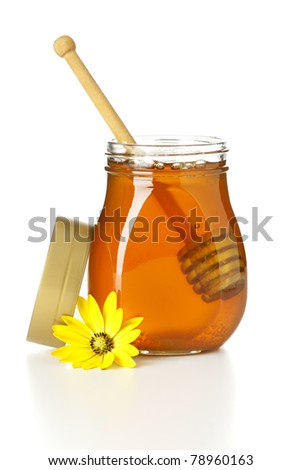opened honey jar with drizzler inside, top and yellow flower aside, isolated on white