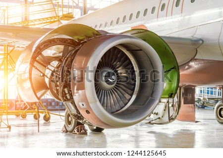 Opened hood aircraft engine jet under maintenance in the hangar