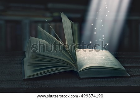 Opened magic book with magic light on a wooden table with bookshelf, invitation to study literatures. The magic of reading or bible and religion. Concept of religion. Christmas fairy-tale. #499374190