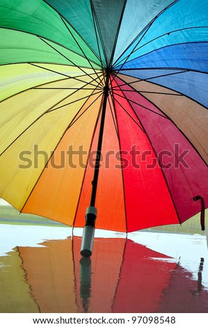Opened multi-colored umbrella with reflection.