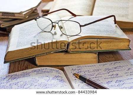 Opened notebook, pen, books and glasses on the wooden table