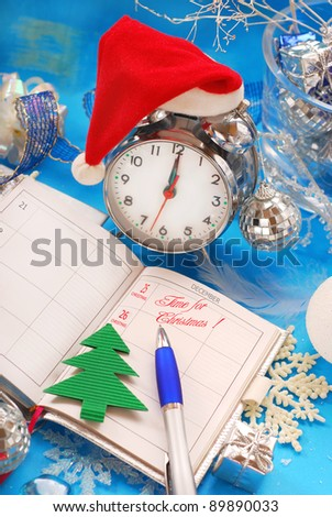 opened notebook with christmas date in calendar and retro alarm clock in santa hat