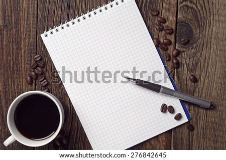 Opened notepad, pen and coffee cup on dark wooden table, top view