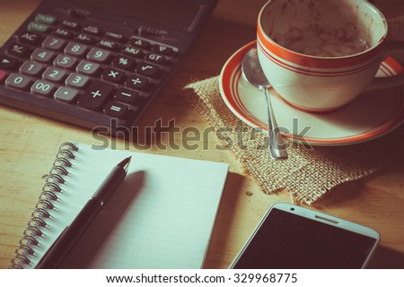 Opened notepad, pen, smart phone, and calculator on wood table in evening time with low key scene and film filter effect