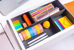 Opened office desk drawer with stationary