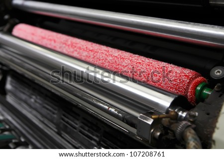 Opened offset printing machine with ink rollers with special red wetting roller. Focused to right side image.