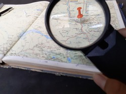 opened old atlas book on map.Atlas and encyclopedia with a magnifying glass on a black background.
