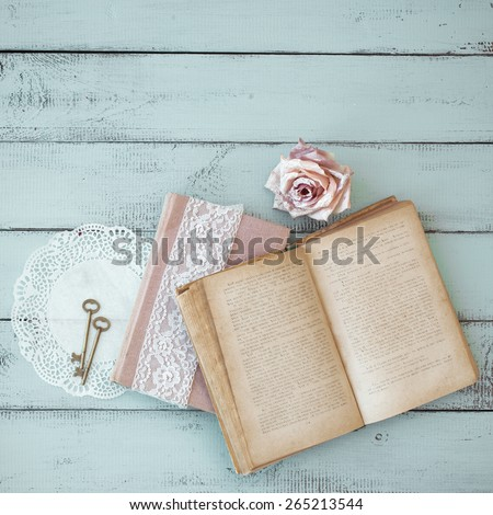 Opened old book with lace, rose and keys on shabby chic mint background, top view point