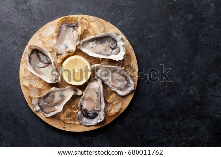 Shutterstock Opened oysters, ice and lemon on wooden board over stone table. Half dozen. Top view with copy space