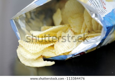 Opened pack of delicious spicy potato chips over black  table. Open bag with potato chips. Potato chips in bag on reflecting background.