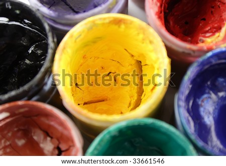 Opened paint buckets with various colors