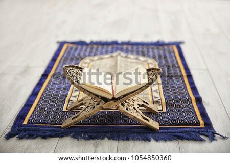 Opened Quran on Muslim prayer mat indoors