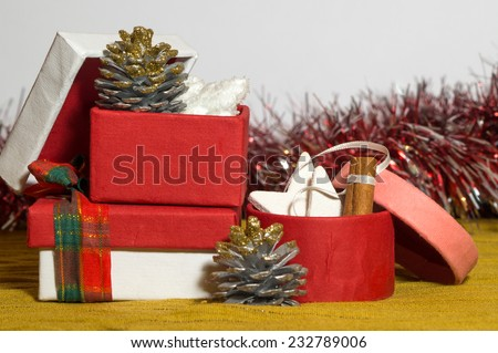 Opened red, pink and white paper Christmas present boxes, they contain Christmas tree decorations