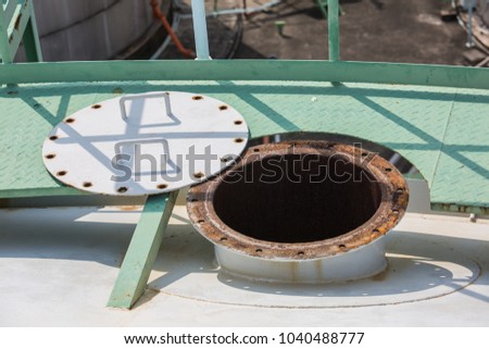 opened rusty manhole on the white fuel tank roof deck storage tank confined space #1040488777