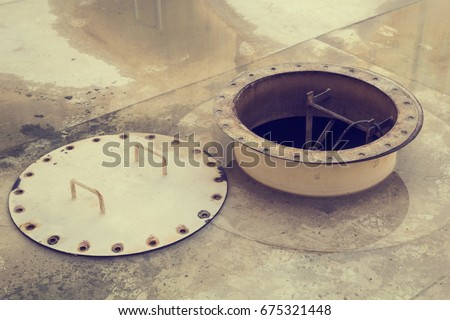 Opened rusty manhole on the white fuel tank roof deck storage tank confined space #675321448