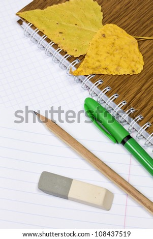 Opened school notebook and pencil, pen, eraser, leaves