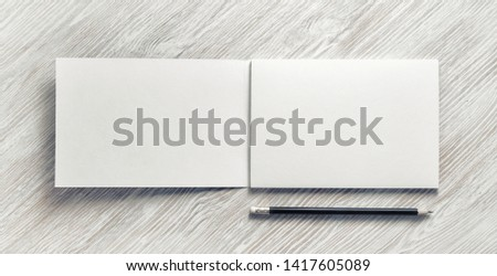 Opened sketchbook with blank pages and pencil on light wood table background. Responsive design template. Flat lay.