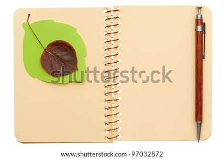 Opened spiral notebook with autumn leaf and pen isolated on white background