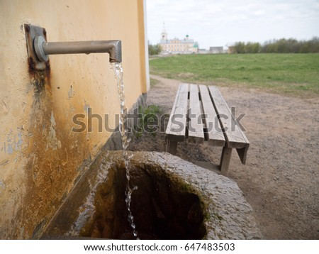 Opened water tap at sacred well at Orthodox monastery in Russia. Save water concept. Water healing concept.  #647483503