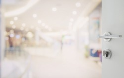 opened white door to shopping mall interior with bokeh as background