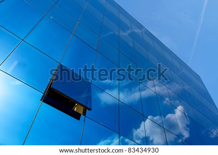 Opened window in the blue skyscraper office building - stock photo