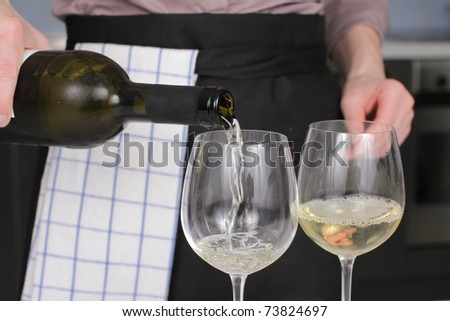 Opening a wine bottle with corkscrew in a kitchen
