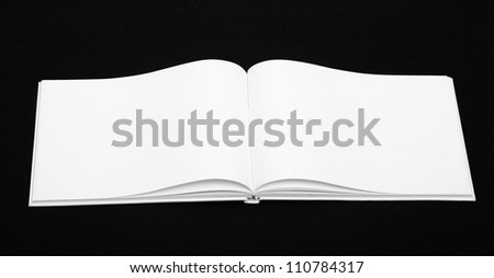 Opening book with blank pages on black background - stock photo