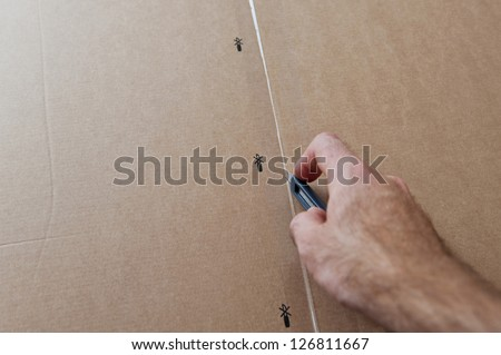 Opening box - man cutting a cardboard box with sharp steel box cutter knife to open it. Concept for parcel delivery, gift opening, moving in, furniture unpacking