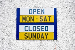 Opening hours shop sign Monday to Friday daytime closed Sunday