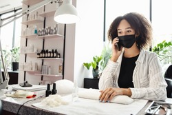 Opening of nail studio after quarantine and taking care of beauty. Millennial african american woman in protective mask speaks on phone, at table with manicure equipment and polish, free space