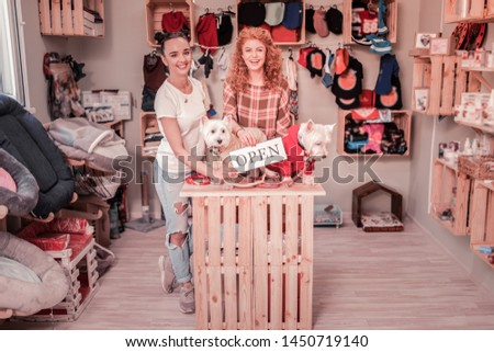 Opening own shop. Two successful young women feeling happy while opening their own shop for pets