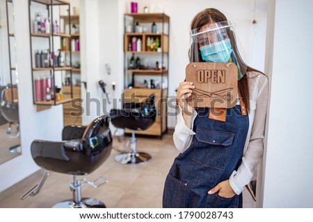 Opening small business after covid-19 pandemic. Portrait of elegant hair salon employee in apron with medical mask, gloves, hair comb and scissors. Hairdressers during COVID-19 Stockfoto ©