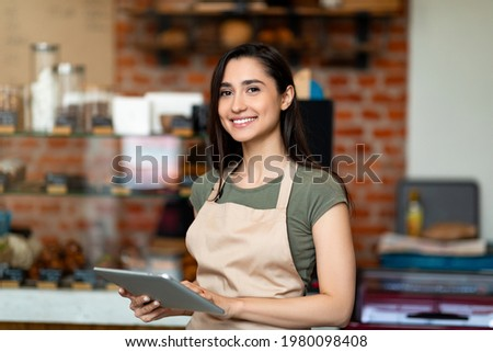 Opening small business. Happy arab woman in apron near bar counter holding digital tablet and looking at camera, waiting for clients in modern loft cafe Foto stock ©