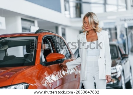 Opening the door. Woman in formal clothes is indoors in the autosalon.