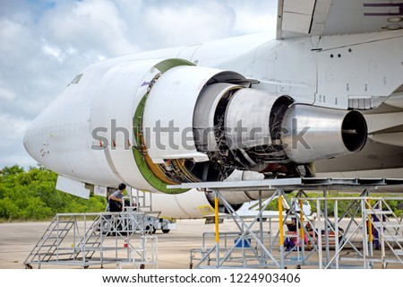 Opening the fan cowling,thrust reverser and core cowling on a jet engine for maintenance before flight.Blue sky clouds.