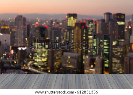 Opening wooden floor, Blurred bokeh light Office building downtown with mountain downtown background