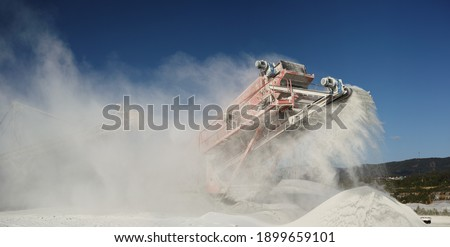 Operating mobile crushing machine with a plume of flying white stone dust against the blue sky, panorama. Foto stock ©