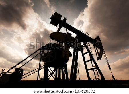 Operating oil and gas well contour, profiled on sky with storm clouds