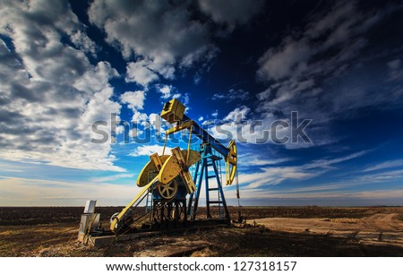 Operating oil well profiled on dramatic cloudy sky Stockfoto ©