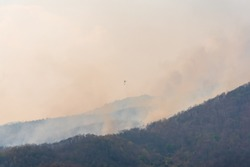Operation to suppress forest fire by helicopter carrying water to pour the bonfire in mountain forests in Chiang Mai province , Thailand.